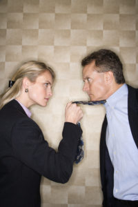 Angry business woman grabbing man by the necktie.