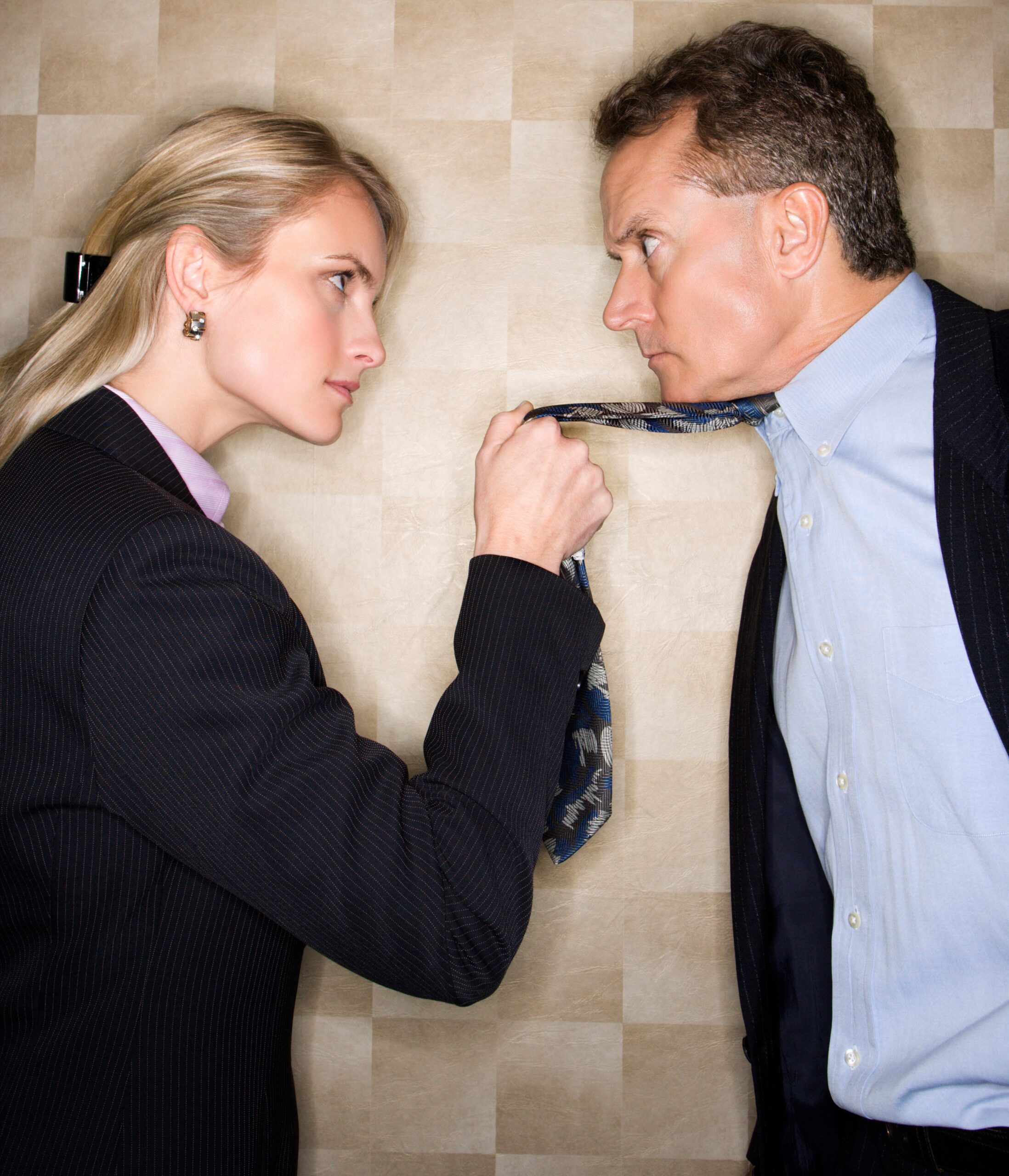 Angry woman pulling man by neck tie