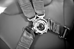 Black and white photo of a seat belt used by race car drivers as readers are cautioned to buckle up for the rest of the blog post.