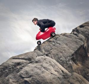 Grown man sitting atop a kitty-car that's careening down mountain