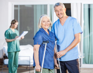 shows woman on crutches receiving care from male nurse