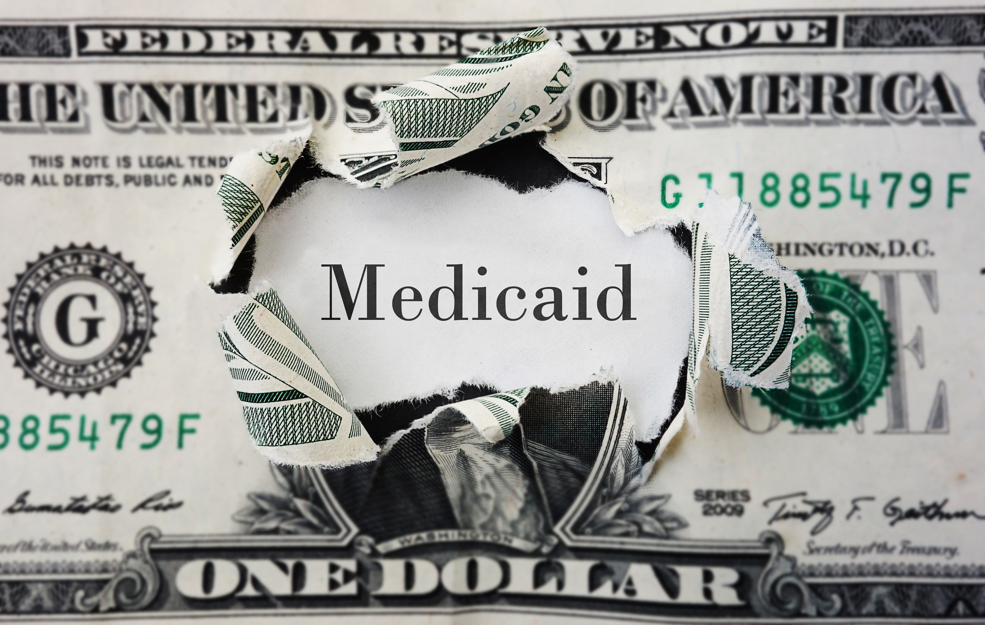 """Torn dollar bill with the word """"Medicaid"""" over George Washington's face"""