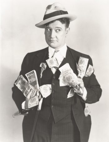 Vintage black and white photo of man holding lots of cash lamenting that he should have planned for inflation and never thought it would take all that cash to buy a loaf of bread.