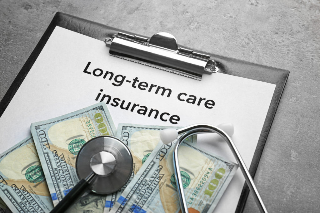Shows words long-term care insurance written on clipboard
