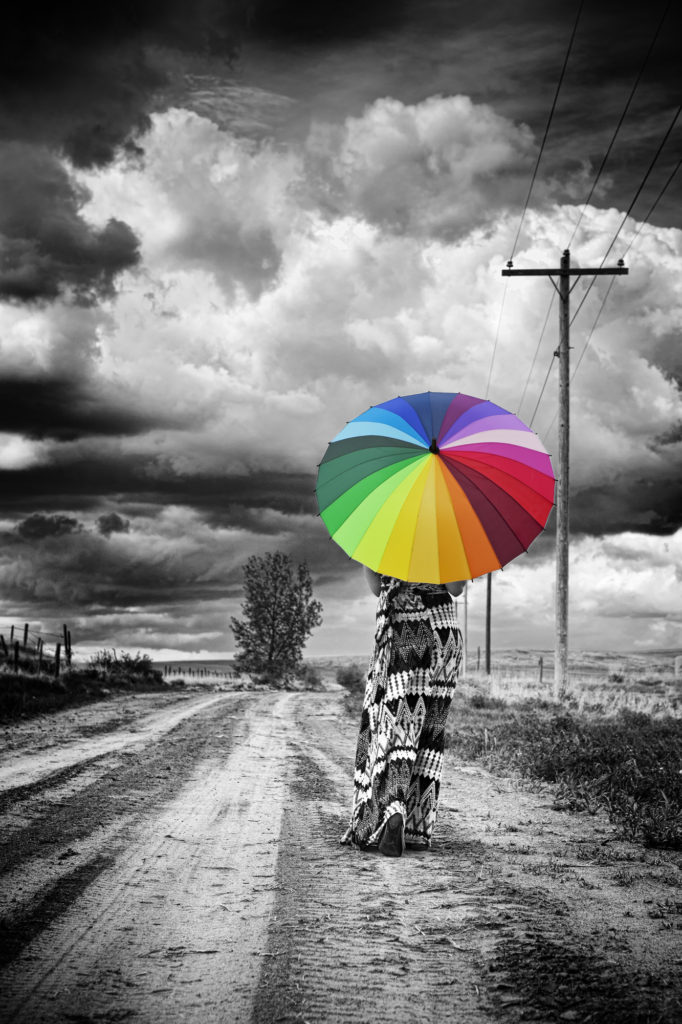 Photo of woman carrying an umbrella that resembles a gay pride flag and is the only item in the photo shot in color.
