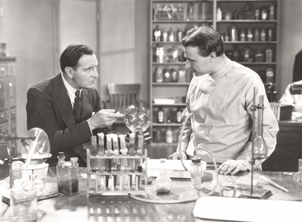 Vintage black and white photo of scientist in his lab talking to a man in a suit.