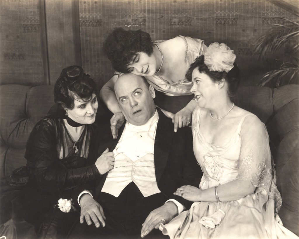 Vintage black and white photo of man being fawned over by three women.