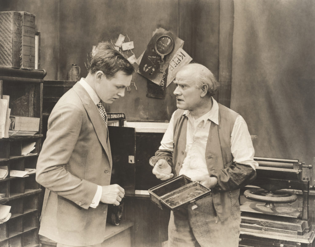 Vintage photo of older man holding an empty strong box while talking to a younger man.