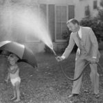 Vintage black and white photo of a toddler holding an umbrella, while her dad in a suit smiles while squirting her umbrella with a hose.
