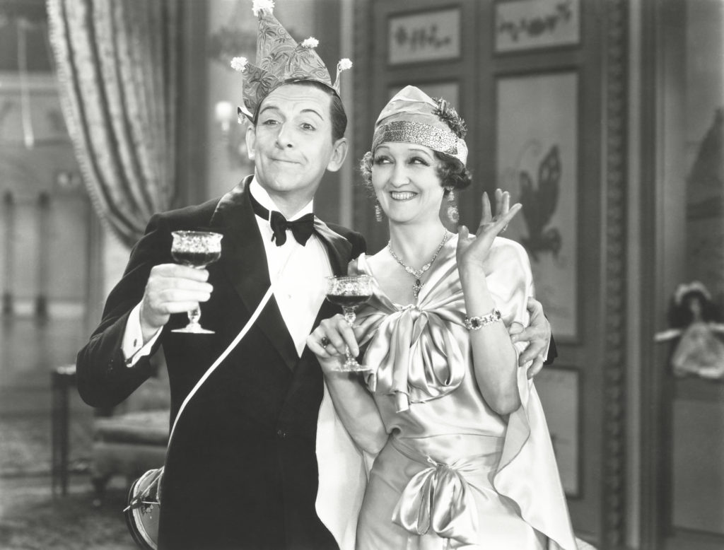Vintage black and white photo of a man and woman holding up their wine glasses and offering a toast.