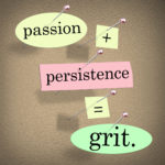 """The words """"Passion Plus Persistence Equals Grit"""" stuck on a bulletin board"""