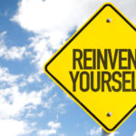 """Blue cloudy sky behind a yellow road sign that says """"reinvent yourself."""""""