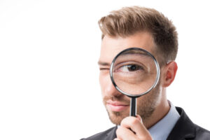 man in suit holding magnifying glass to his eye symbolizing to know how to navigate Medicaid.
