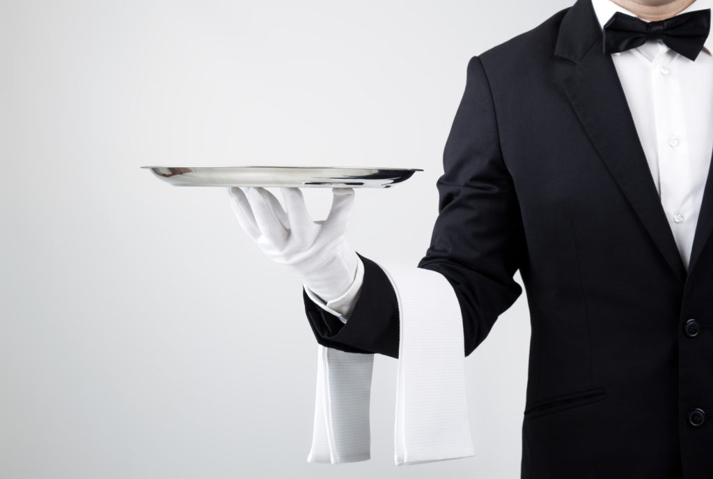 Torso of elegant waiter holding an empty silver serving tray in his palm.