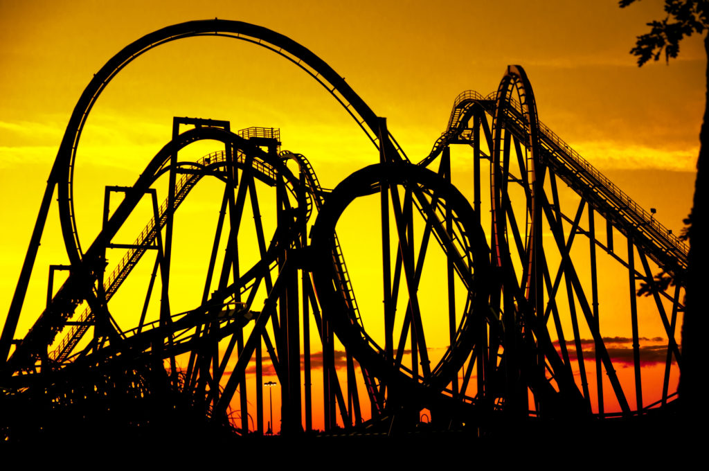 Outline of a roller coaster against a golden sunset.