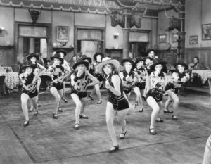 Vintage black and white photo of saloon dancers performing routine