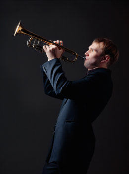 Photo of man playing trumpet against black background