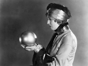 Vintage photo of woman fearful she'll outlive her money so she's asking the crystal ball where her money went.