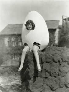 Vintage black and white photo of woman sitting inside her giant nest-egg, happy because she knows she won't outlive her money.