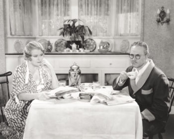 Vintage black and white photo of a couple at the breakfast table contemplating a move to a continuing care retirement community