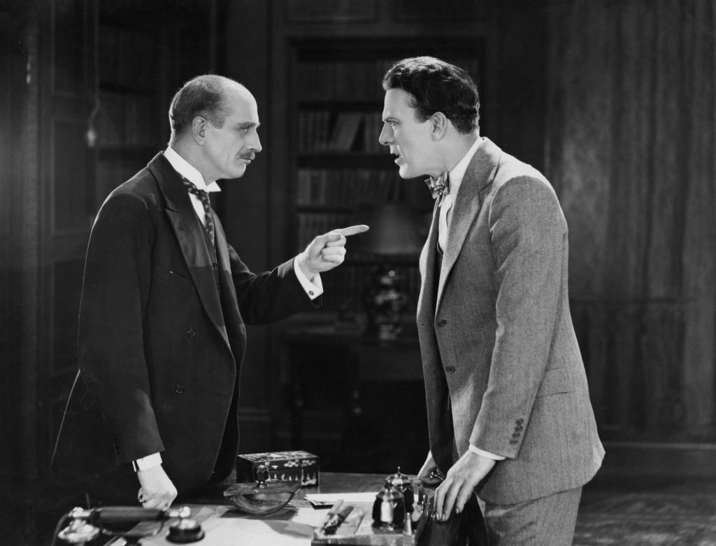 Vintage black and white photo of two men in office arguing about continuing care retirement communities