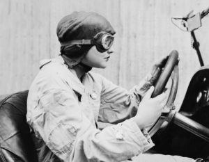 Vintage photo of a female driving open air car wearing an aviator mask and hat on her way to a continuing care retirement community.