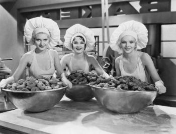 Vintage photo of three female chefs, holding freshly baked donuts in a continuing care retirement community.