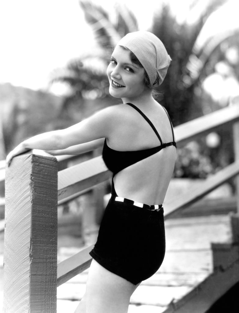Vintage black and white photo of a woman in a bathing suit and bathing cap smiling because she lives in a continuing care retirement community.