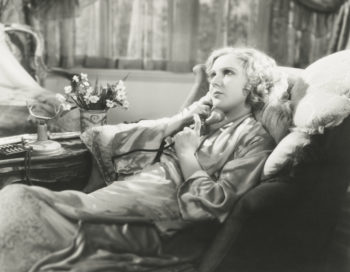 Black and white photo of woman in silk pajamas, talking on phone to a continuing care retirement community.