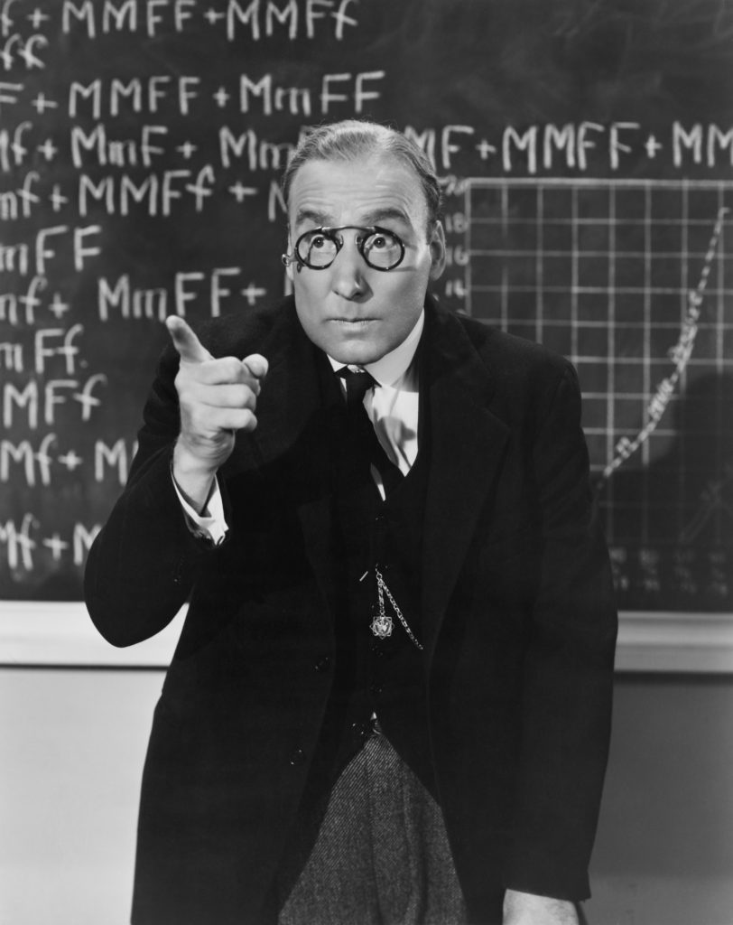 Vintage black and white photo of professor in front of chalk board.
