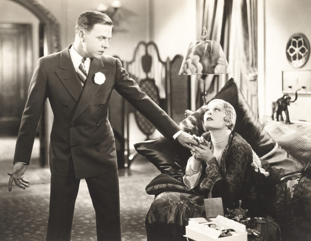Vintage photo of woman holding a man's grabbing man's hand and begging him to tell her if she has enough money to retire.