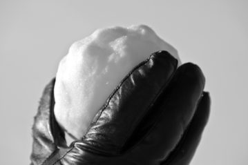 black and white photo of gloved hand holding a snowball, representing Dave Ramsey's debt snowball technique
