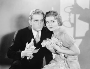 Vintage black and white photo of couple clutching money they want to keep out of the stock market. because of the Corona Virus effect on their nest-egg.