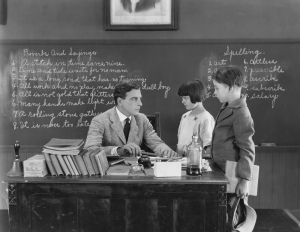 Black and white retro photo of a teacher lecturing two students at his desk, symbolizing that deliberate purposeful practice often requires a teacher or mentor.