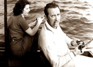 Well dress man and woman fishing off a boat, as man looks apprehensively off camera.