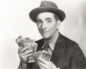 Black & white vintage photo of man holding the gob's of money he gets from his deceased wife's annuity because she asked one of the 11 critical questions before she bought an annuity.