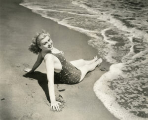 Retro black and white photo of woman sitting on the beach letting the waves hit her feet as she looks fetchingly at the camera.