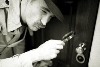 Black and white retro photo of detective with magnifying glass symbolizing looking over the free look period.