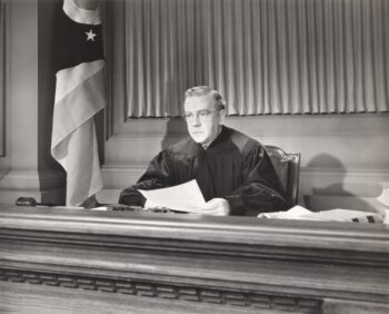 Black and white retro photo of judge describing process for handling an annuity bankruptcy.
