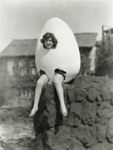 Retro black and white photo of woman with her head and legs sticking out of a giant nest-egg, wondering if she should buy an immediate or longevity annuity.