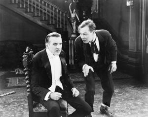 Black and white retro photo of one man berating his older partner about not following the three must-do actions to avoid annuity bankruptcy.