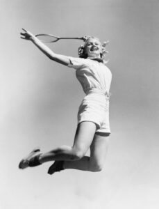 Black and white retro photo of woman who is leaping in air because she got a refund after her annuity declared bankruptcy.