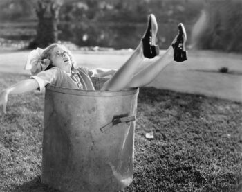 Retro black and white photo of woman sitting in a giant bucket, realizing this isn't the bucket strategy for making your money last.