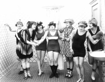 Retro black and white photo of women in their bathing suits serving as social security to one another.