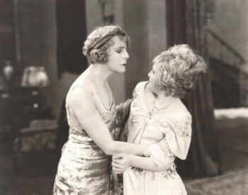 Retro black and white photo of two women grabbing one another arguing over equity indexed annuities.