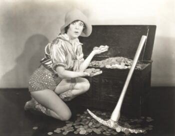 Retro black and white photo of woman kneeling at a treasure chest full of gold coins lamenting that it takes an entire chest of gold coins to buy a simple loaf of bread.