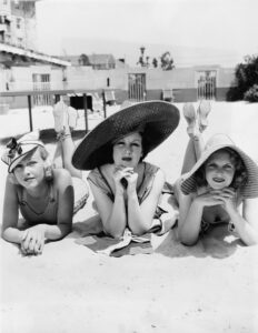 Retro black and white photo of three woman sunbathing on beach as one opines on the appeal of her boyfriend's immediate and longevity annuities.
