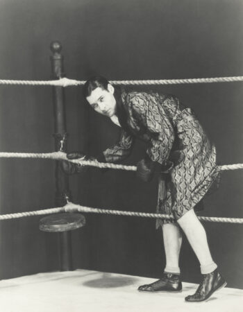 Black and white retro photo of boxer stepping in the ring symbolizing the author of the Psychology of Money and how he's been punching above his weight for years.