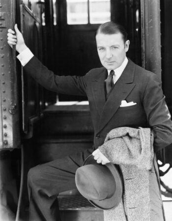 Black and white retro photo of wealthy looking man boarding a train.