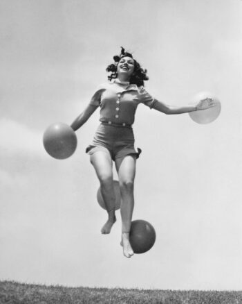 Woman in bathing suit jumping in air with balloon.